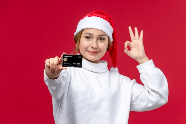Front view young female with bank card on red background