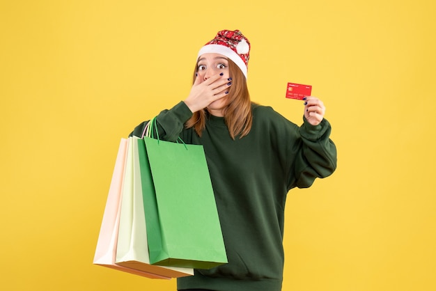 Front view young female with bank card and shopping packages