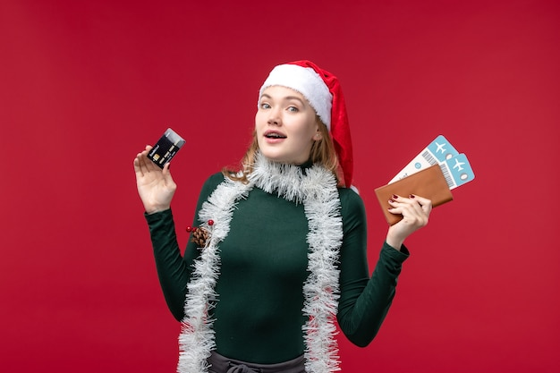 Giovane donna di vista frontale con carta di credito e biglietti su sfondo rosso