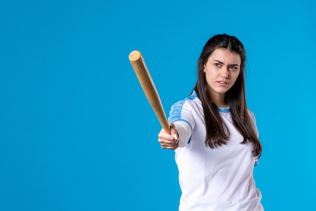Front view young female with baseball bat on blue wall