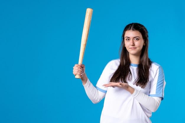 青い壁に野球のバットと正面図若い女性