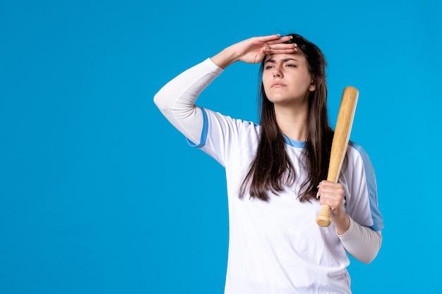 Вид спереди молодая женщина с бейсбольной битой на синей стене