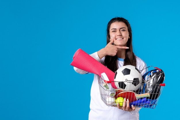 Front view young female with basket after sport shopping blue wall