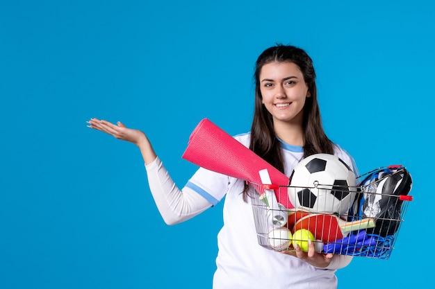 青い壁でスポーツショッピング後のバスケットを持つ若い女性の正面図
