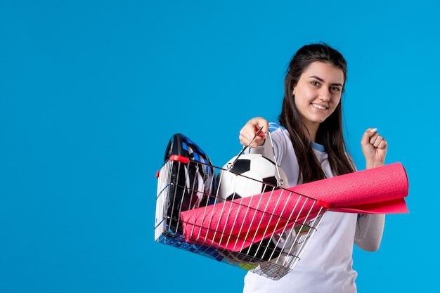 파란색 벽에 스포츠 쇼핑 후 바구니와 함께 전면보기 젊은 여성