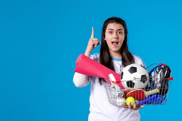 Вид спереди молодая женщина с корзиной после спортивных покупок на синей стене