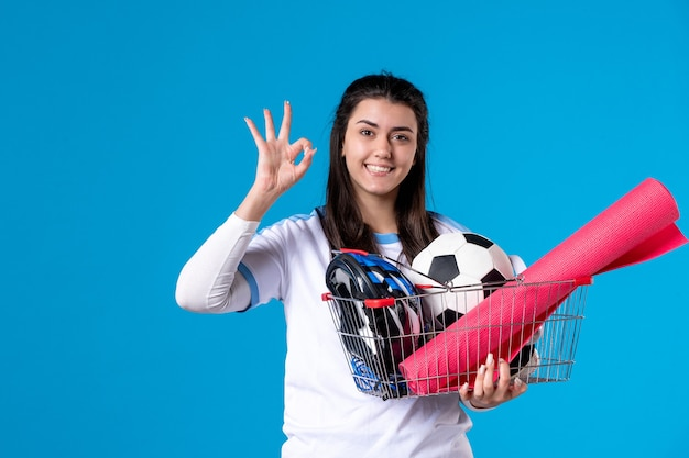 Front view young female with basket full of sport things blue wall