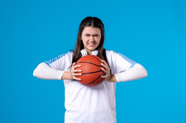 Front view young female with basketball on blue wall