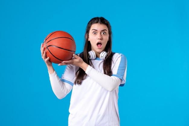 Вид спереди молодая женщина с баскетболом на синей стене