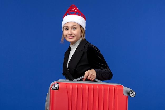 青い壁に大きな赤いバッグと正面図若い女性年末年始休暇の色