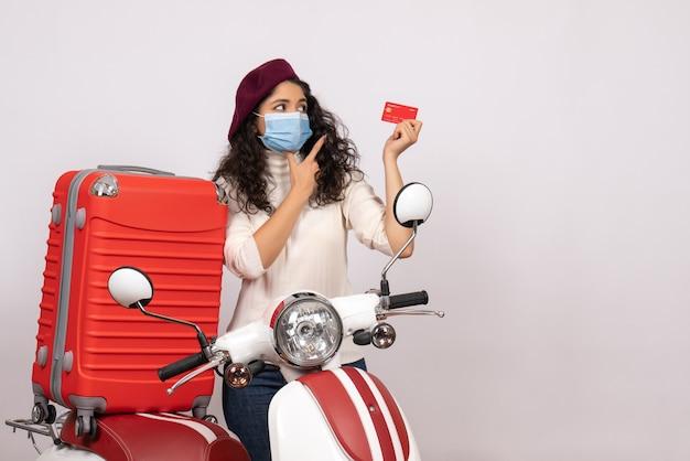 Vista frontale giovane donna con bici in possesso di carta di credito rossa su sfondo bianco colore covid- virus del veicolo pandemia moto velocità strada