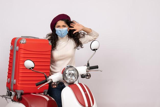Vista frontale giovane donna con bici in maschera su sfondo bianco colore covid-velocità veicolo moto virus