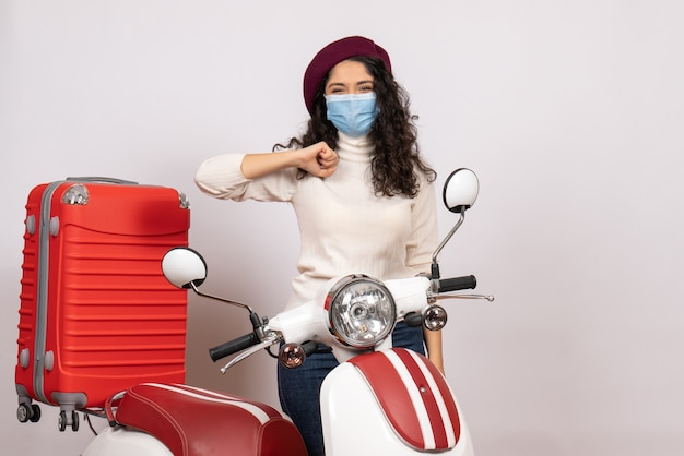 Vista frontale giovane donna con bici in maschera su sfondo bianco colore virus velocità covid- motocicletta veicolo pandemico