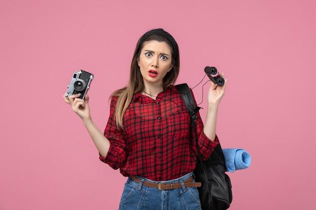 Vista frontale giovane femmina con il binocolo e la macchina fotografica su sfondo rosa colore donna umana