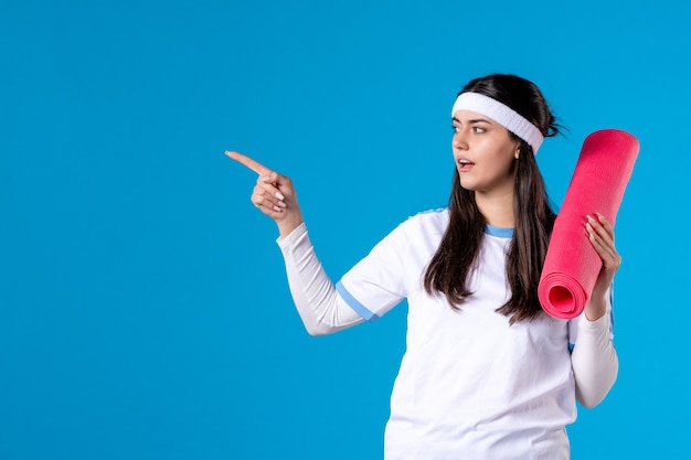 Giovane donna di vista frontale con tappeto per esercizi sulla parete blu