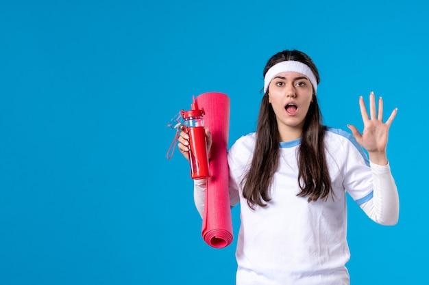 エクササイズ用カーペットと青い壁に水のボトルと正面図若い女性