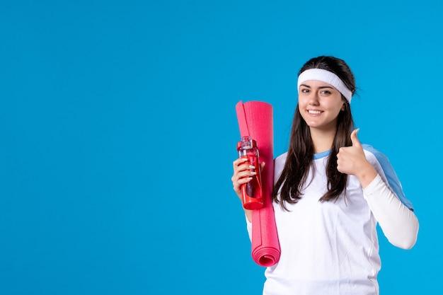 Вид спереди молодая женщина с ковром для упражнений и бутылка воды на синей стене