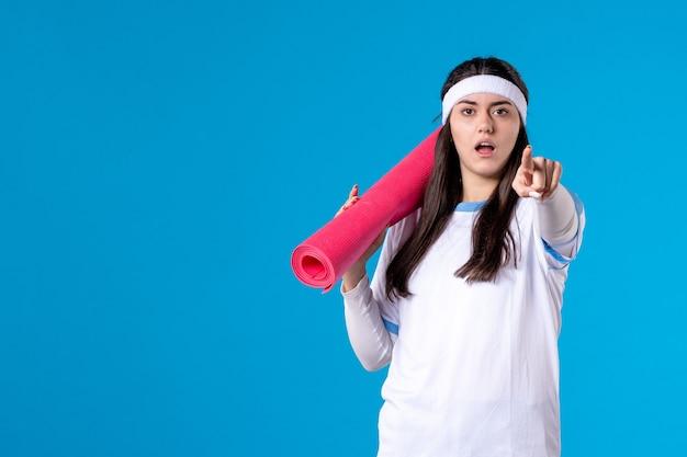 青い壁の練習のためのカーペットと正面図若い女性