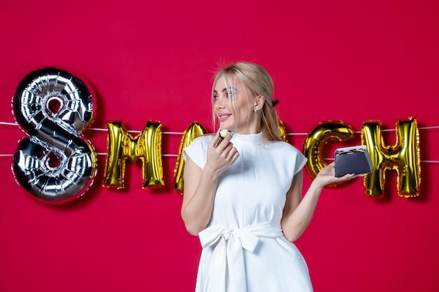 3月にチョコレート菓子で飾られた赤い背景のビジネスパーティーの平等官能的な女性の女性の日の楽しい休日の正面図若い女性