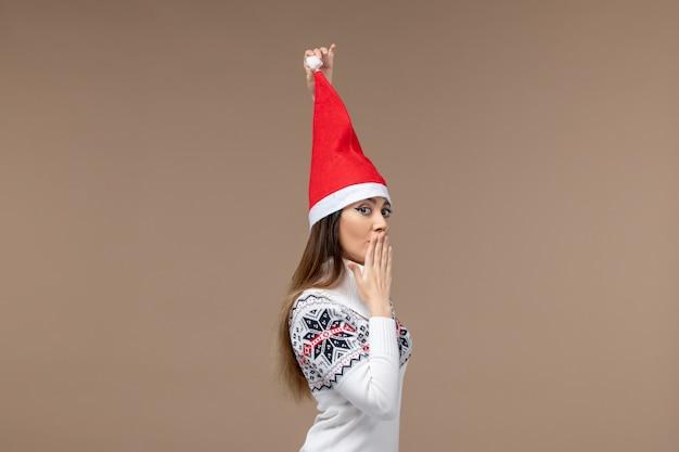 茶色の背景の休日のクリスマスの感情にクリスマスキャップと正面図若い女性