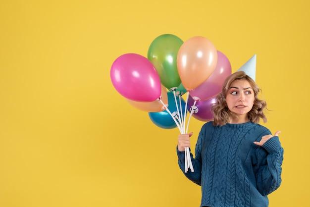 カラフルな風船と正面図若い女性