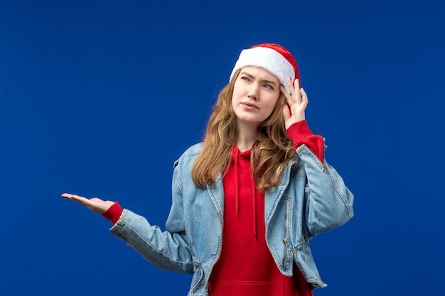 Vista frontale giovane femmina con espressione confusa su sfondo blu colore di emozioni di natale