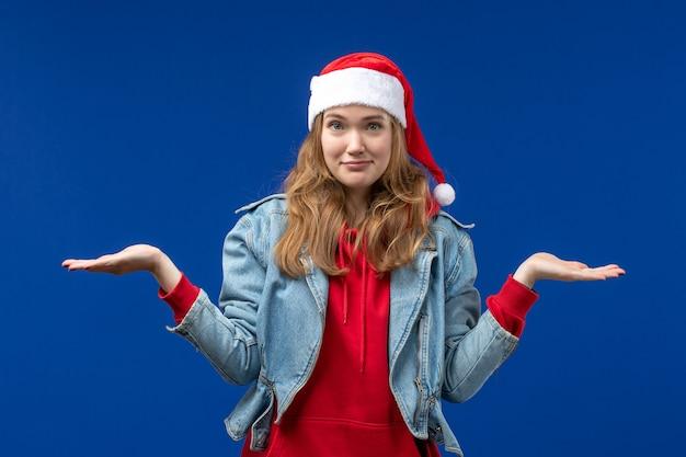 Вид спереди молодая женщина с растерянным выражением лица на синем фоне цвета рождественских эмоций