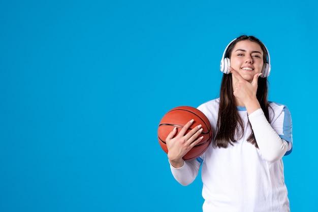 Giovane femmina di vista frontale con gli auricolari che tengono la pallacanestro sulla parete blu