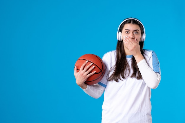 Front view young female with earphones holding basketball on blue wall