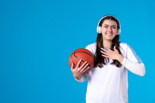 青い壁にバスケットボールを保持しているイヤホンを持つ若い女性の正面図