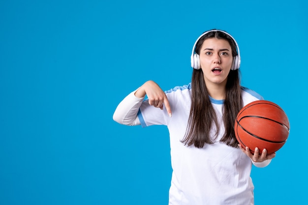 이어폰 파란색 벽에 농구를 들고 전면보기 젊은 여성