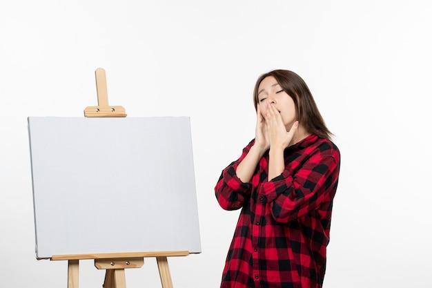 Vista frontale giovane donna con cavalletto per disegnare sbadigli sul muro bianco