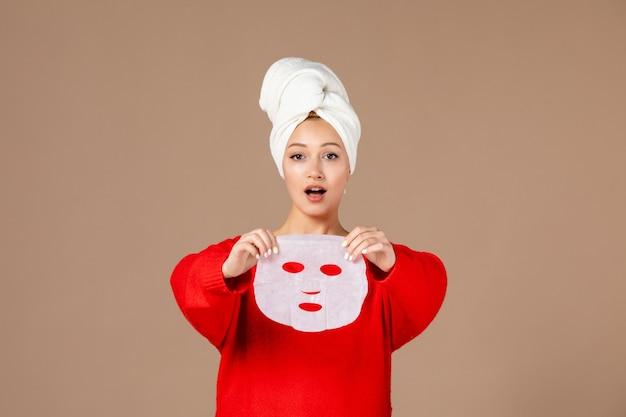 Vista frontale giovane femmina con maschera per il viso nelle sue mani su sfondo rosa