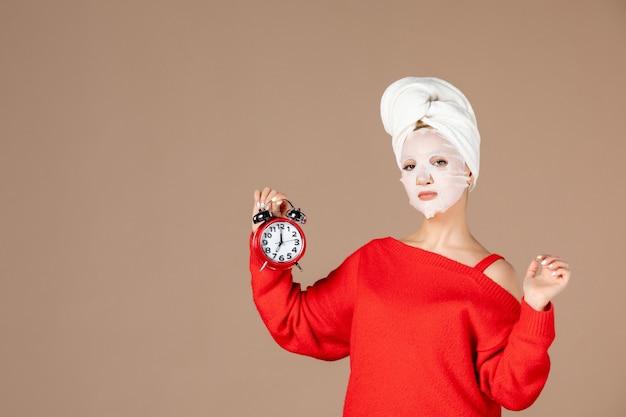ピンクの背景に時計を保持しているフェイスマスクと正面図若い女性
