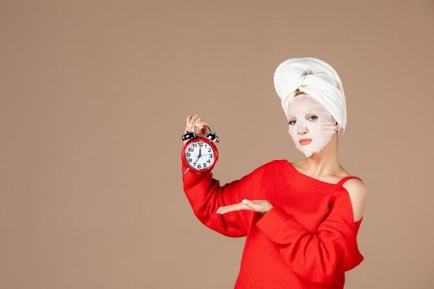 Vista frontale giovane femmina con maschera facciale tenendo l'orologio su sfondo rosa