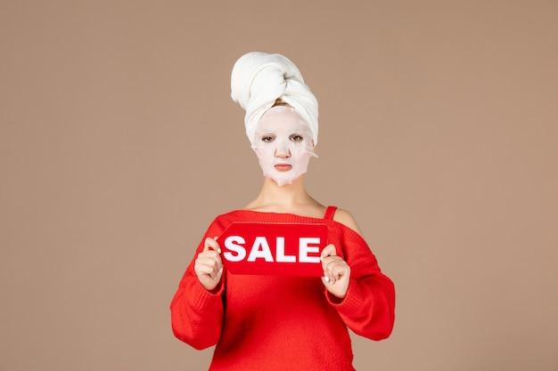 Vista frontale giovane femmina con maschera facciale tenendo la targhetta di vendita su sfondo rosa