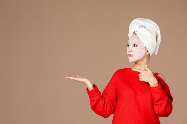 Vista frontale giovane femmina con maschera facciale su sfondo rosa