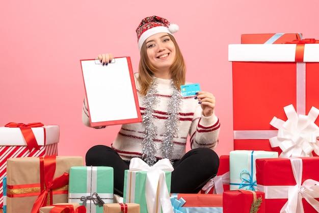 ファイルノートと銀行カードを持つ正面図若い女性