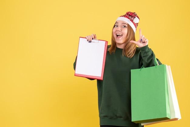 ファイルメモとショッピングパッケージと正面図の若い女性 無料写真