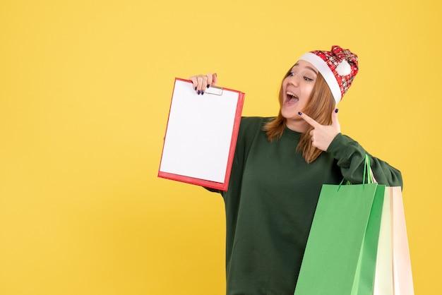 ファイルメモとショッピングパッケージと正面図の若い女性