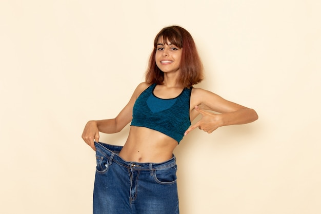 Front view of young female with fit body in blue shirt checking her weight on light-white wall