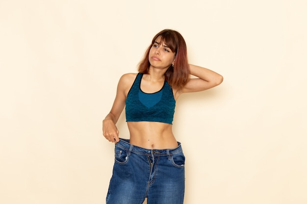 Vista frontale della giovane donna con un corpo in forma in camicia blu che controlla il suo peso sul muro bianco chiaro