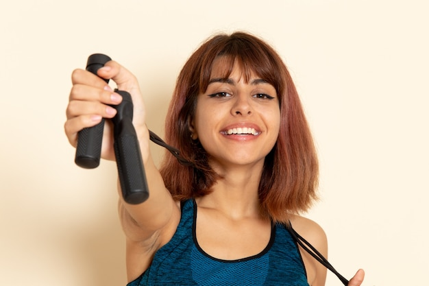 Front view of young female with fit body in blue shirt holding skipping ropes on light-white wall