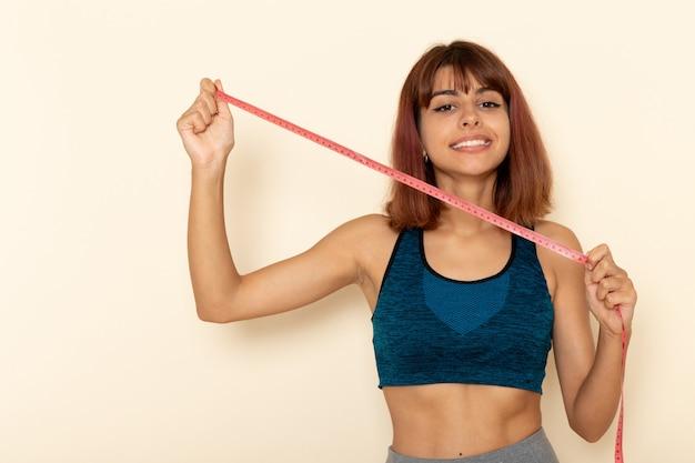 Vista frontale della giovane donna con un corpo in forma in camicia blu che tiene la misura della vita sul muro bianco chiaro