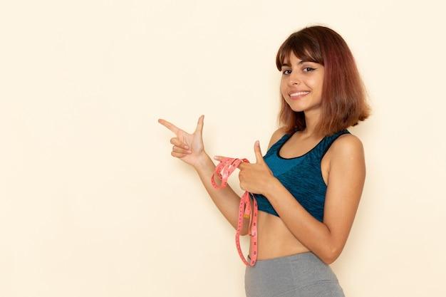 Vista frontale della giovane donna con corpo in forma in camicia blu che tiene la misura della vita con il sorriso sul muro bianco chiaro