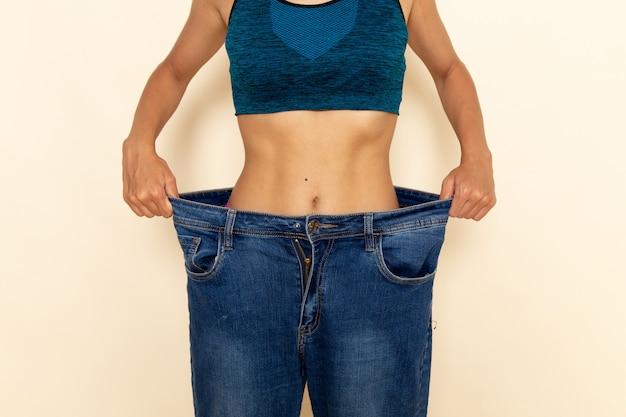 Vista frontale di giovane donna con corpo in forma in camicia blu e jeans sulla parete bianco-chiaro