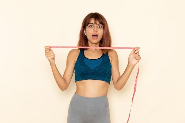 Vista frontale della giovane donna con un corpo in forma in camicia blu che misura la sua vita sul muro bianco chiaro