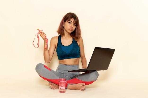 Vista frontale della giovane donna con corpo in forma in camicia blu utilizzando il suo computer portatile sulla parete bianca leggera