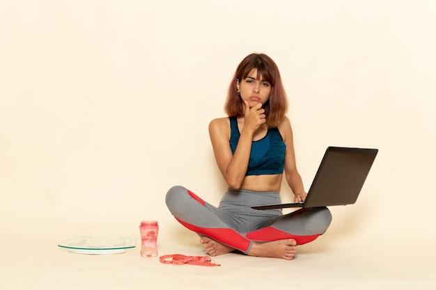 Vista frontale di giovane donna con corpo in forma in camicia blu utilizzando laptop sulla parete bianca leggera
