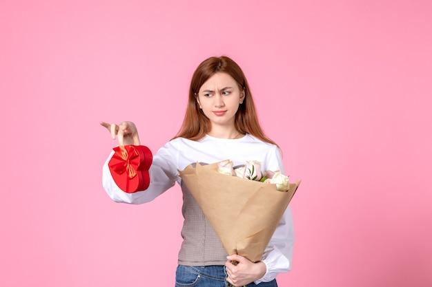Вид спереди молодой женщины с цветами и подарком на женский день на розовом фоне, горизонтальное равенство марша, женское свидание, роза, женщина, любовь